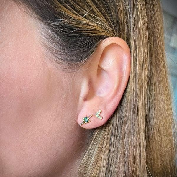 Gold Lightning Bolt Stud Earring with Rainbow Colored stones shown on model ear. Image is zoomed in on ear. Model has light brown hair. Model is also wearing a Chevron pave stud earring in her second earring hold