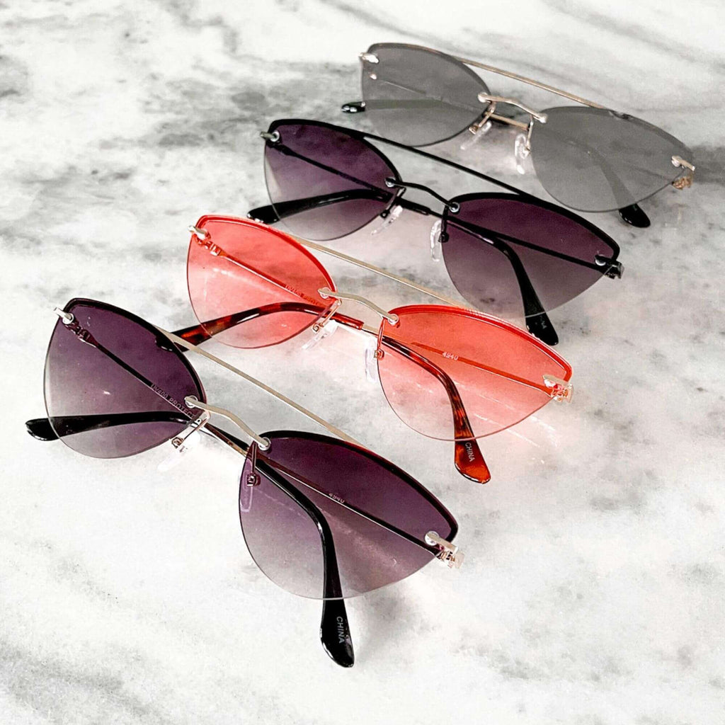 Metal cateye sunglasses in red, black and gold shot on marble table.