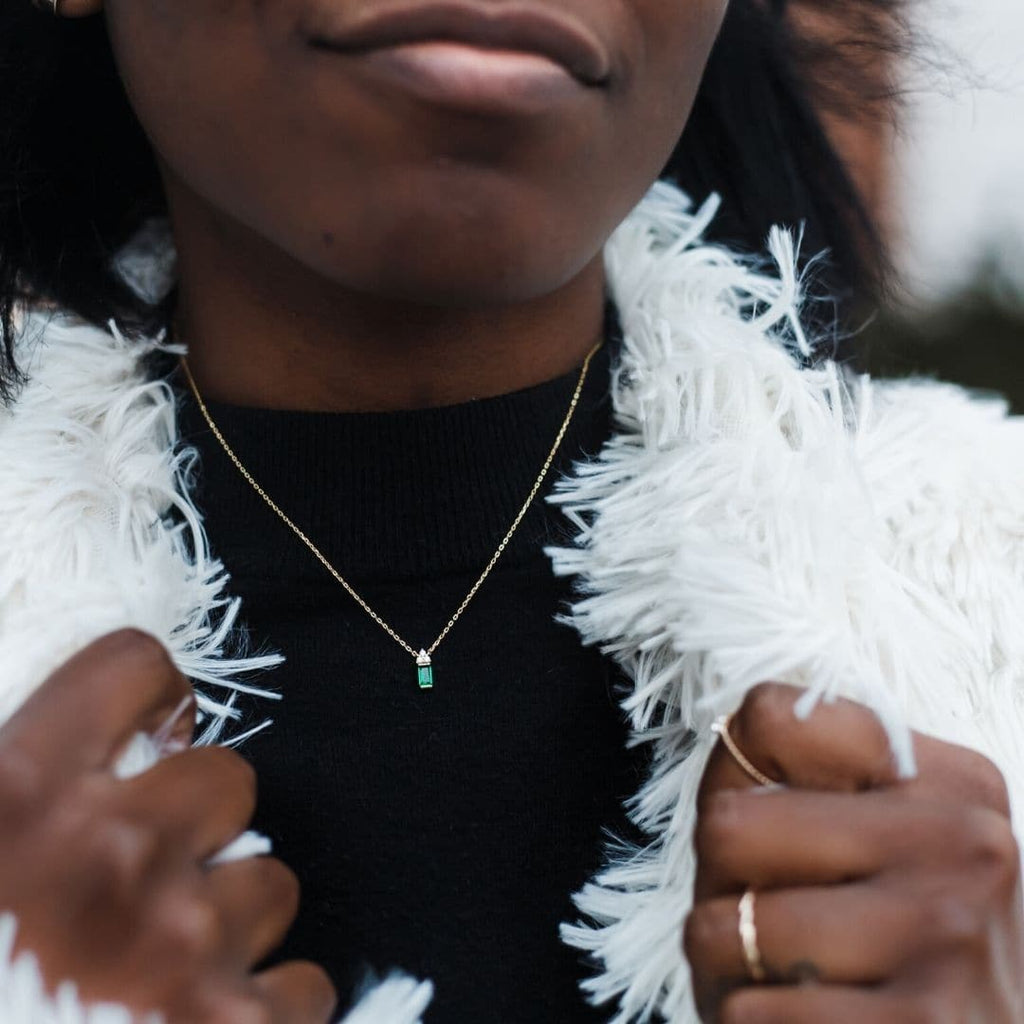Elliott Gold and Emerald Green dainty necklace shown on african american model who is wearing a black mock turtleneck and white fuzzy shawl.