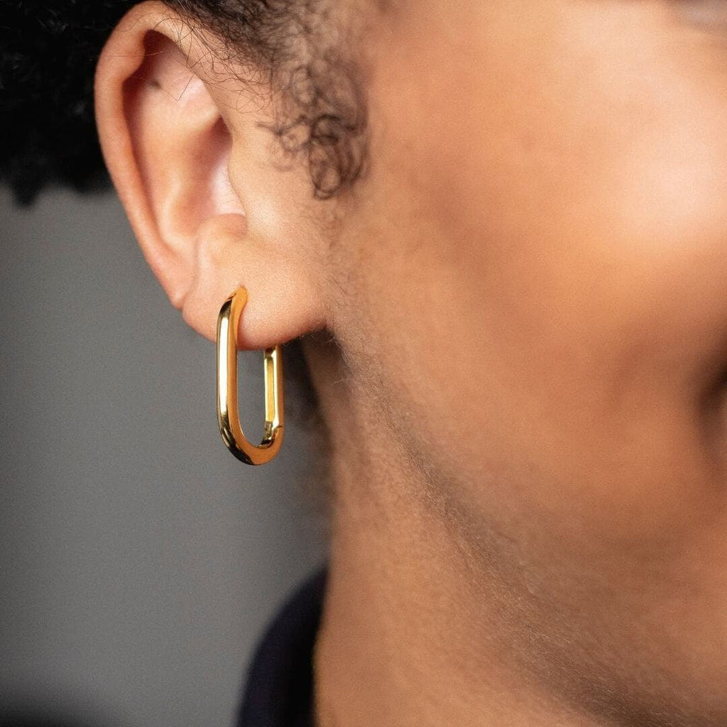Gold Oblong Oval Hoop Earring shot on model ear. Image is zoomed in on Black models' ear with black turtleneck.
