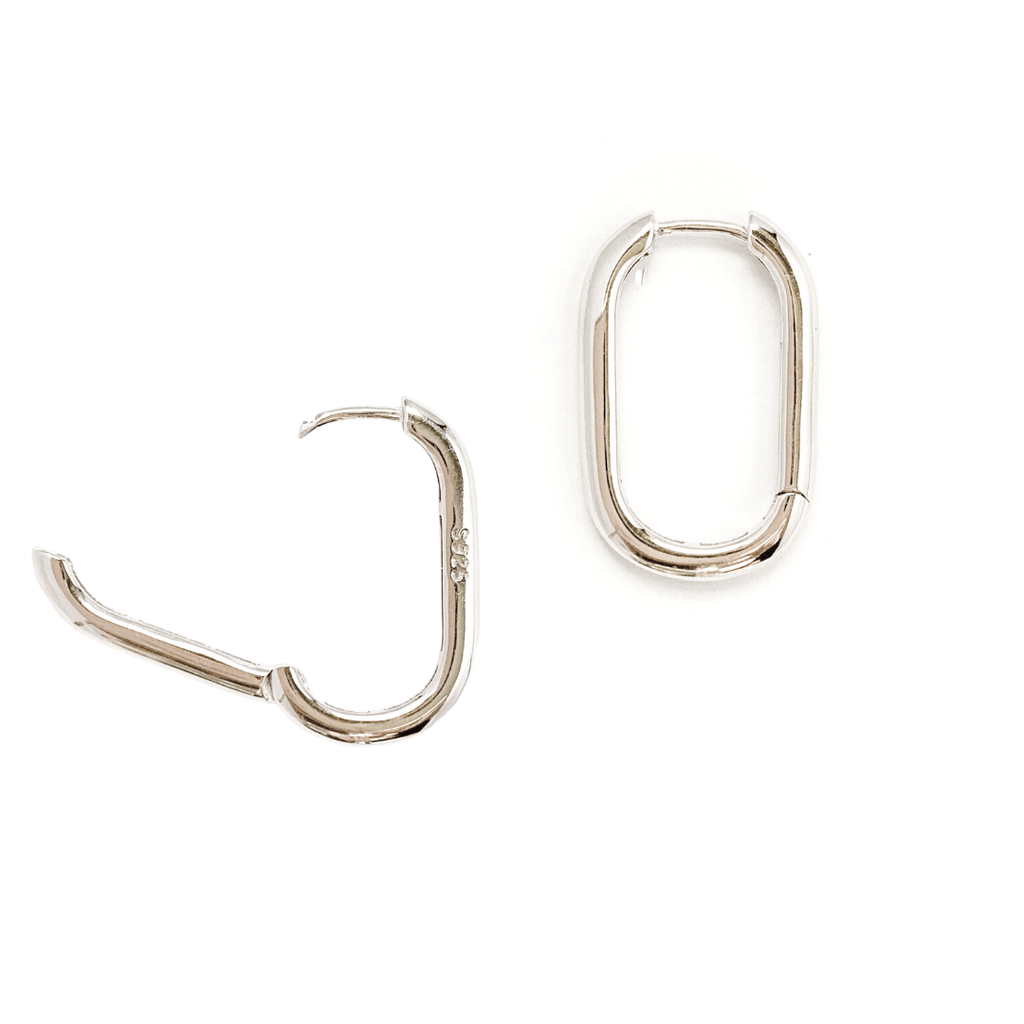 Sterling Silver oblong oval hoop earrings shot on white background. Left earring is featured in open position displaying hinge closure and  S925 hallmark.
