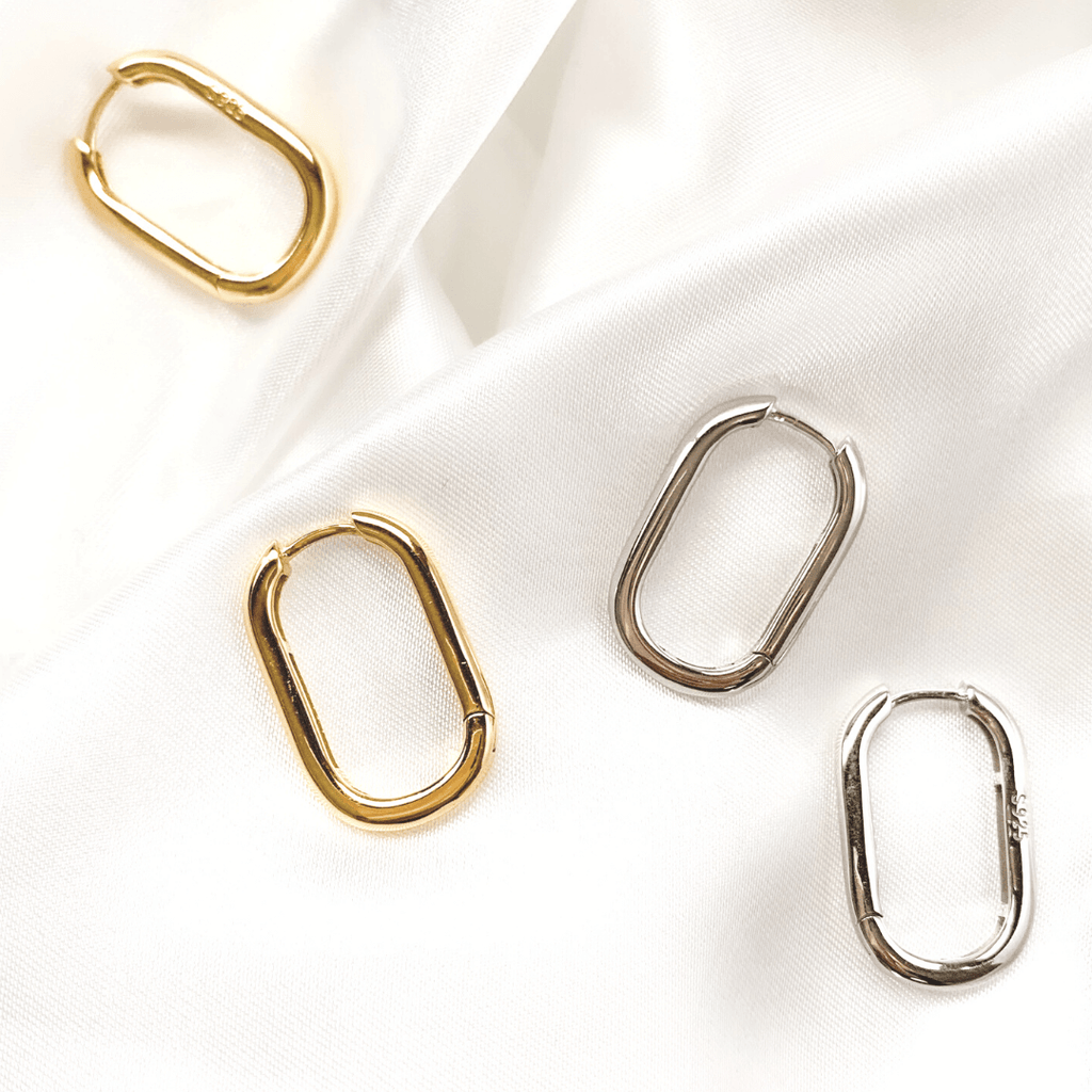 Silver and Gold Medium Oval hoop earrings shot on white satin sheet.