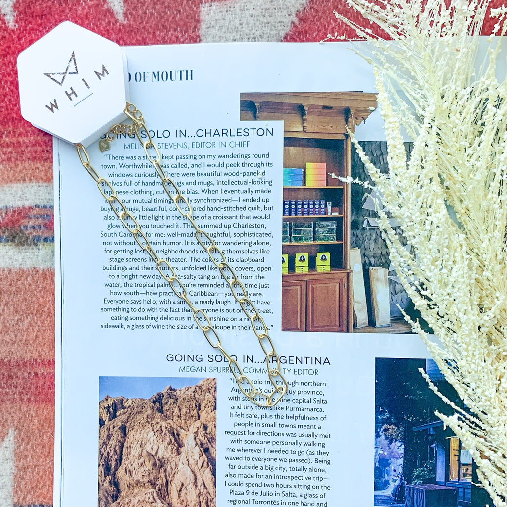"Bronson Gold Small Chain Link Choker show in hexagon packaging with ""Whim"" in rose gold. Necklaces is laid on travel magazine surrounded by natural elements."