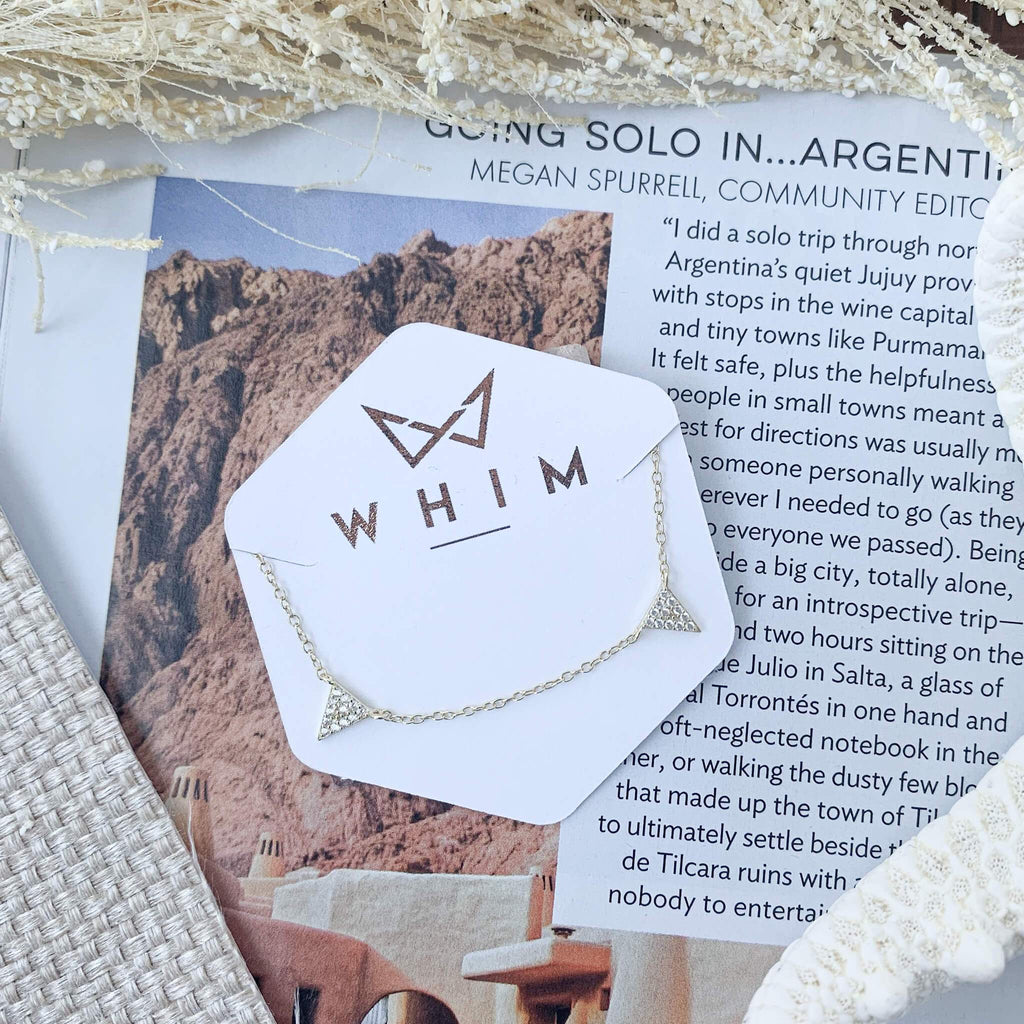 "Victoria Triangle Charm Gold Choker shown in hexagon packaging reading ""Whim"" in rose gold and laid on top of a travel magazine."