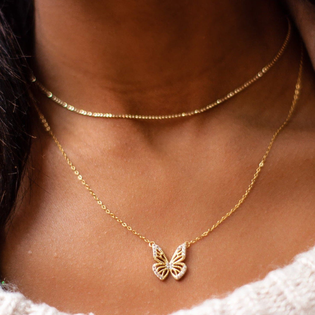 Monarch Gold Butterfly Necklace shot on model. Model is also wearing Paris Choker and a white sweater