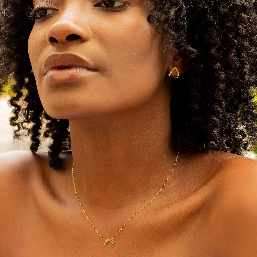 Oz Gold mini rainbow choker shot on a black female model with natural hair. The necklace is show draping just below the collarbone. The Model is wearing a light blue off the should shirt. She is also wearing our Bermuda Chevron Huggie Earrings