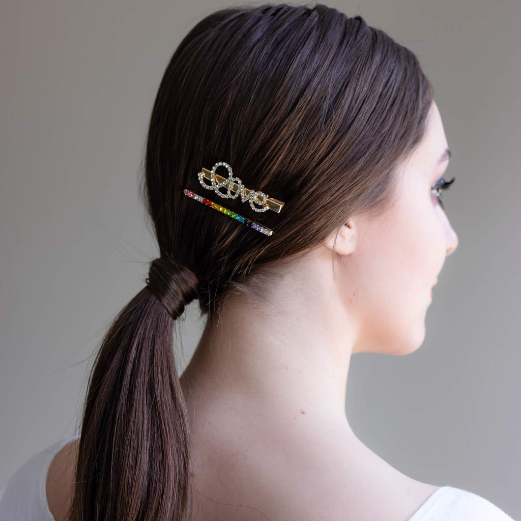 Love Butterfly Hair Pin and Rainbow Rhinestone Bobby Pin shot on brunette model above a low ponytail.