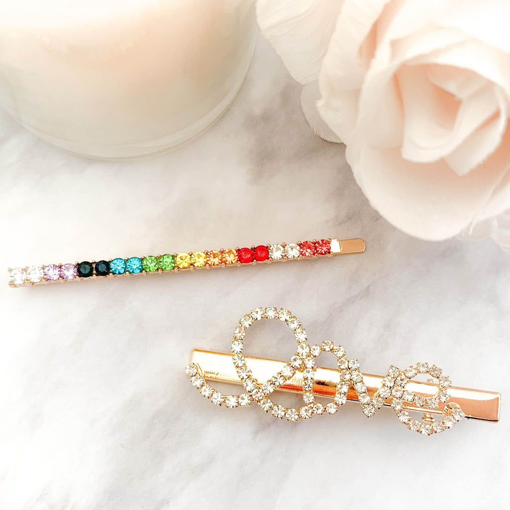 Rainbow Rhinestone bobby pin and bobby pin that reads 'love' in cursive. Shot on marble counter next to a candle and rose. This comes in a set of two hair pins.