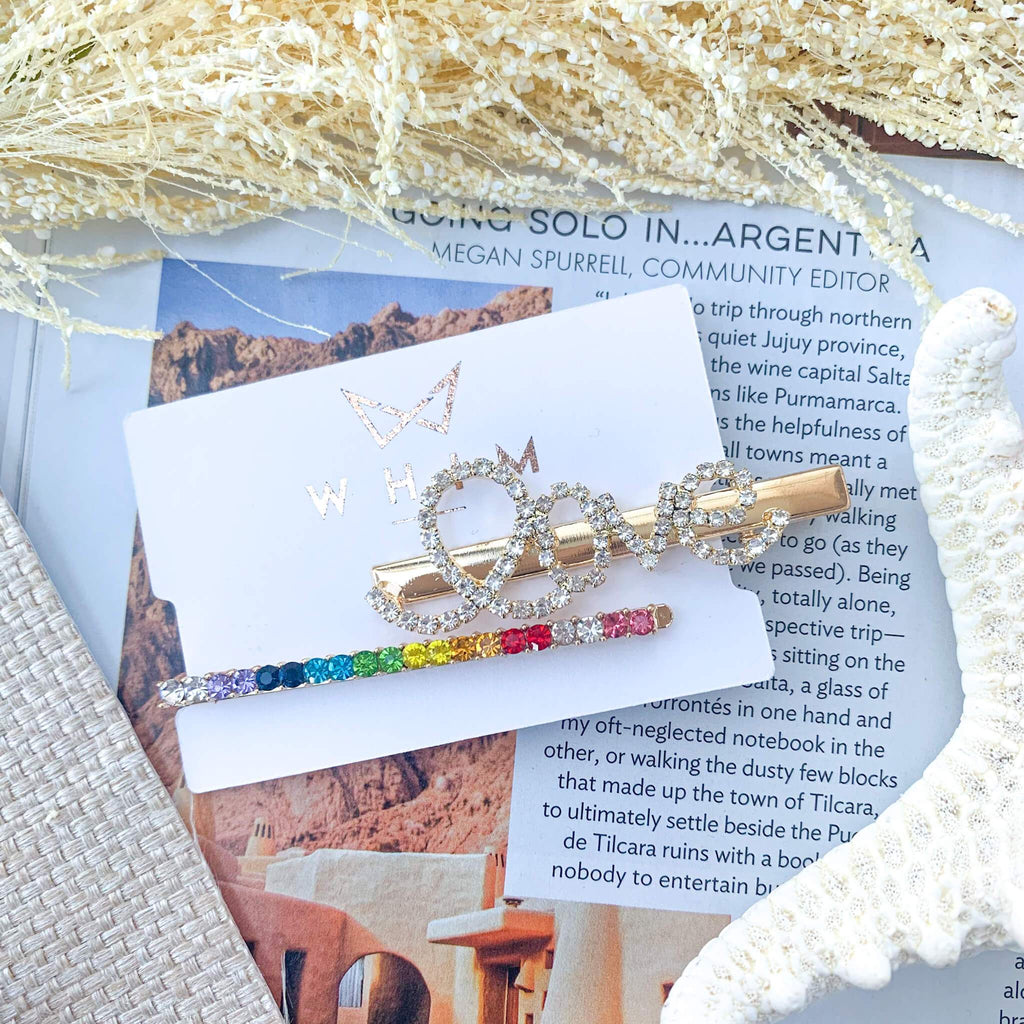"Rainbow Love Bobby pin set shot in packaging that reads ""Whim"". Shot on a travel magazine with natural elements."