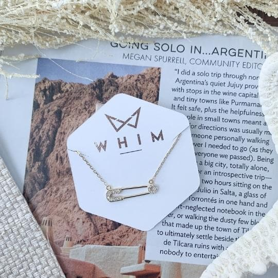 Melbourne Pave Safety Pin Choker necklace shot in whim collection packaging with travel magazine and natural elements