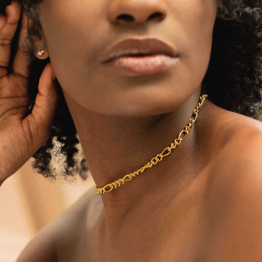 Cartagena Chain Choker is shot on model with natural hair. Model is looking to the right and wearing an off the shoulder blue flowing top. The photo is shot in an urban environment with lots of green space. Model is also wearing Twin Cities Stud Earrings.