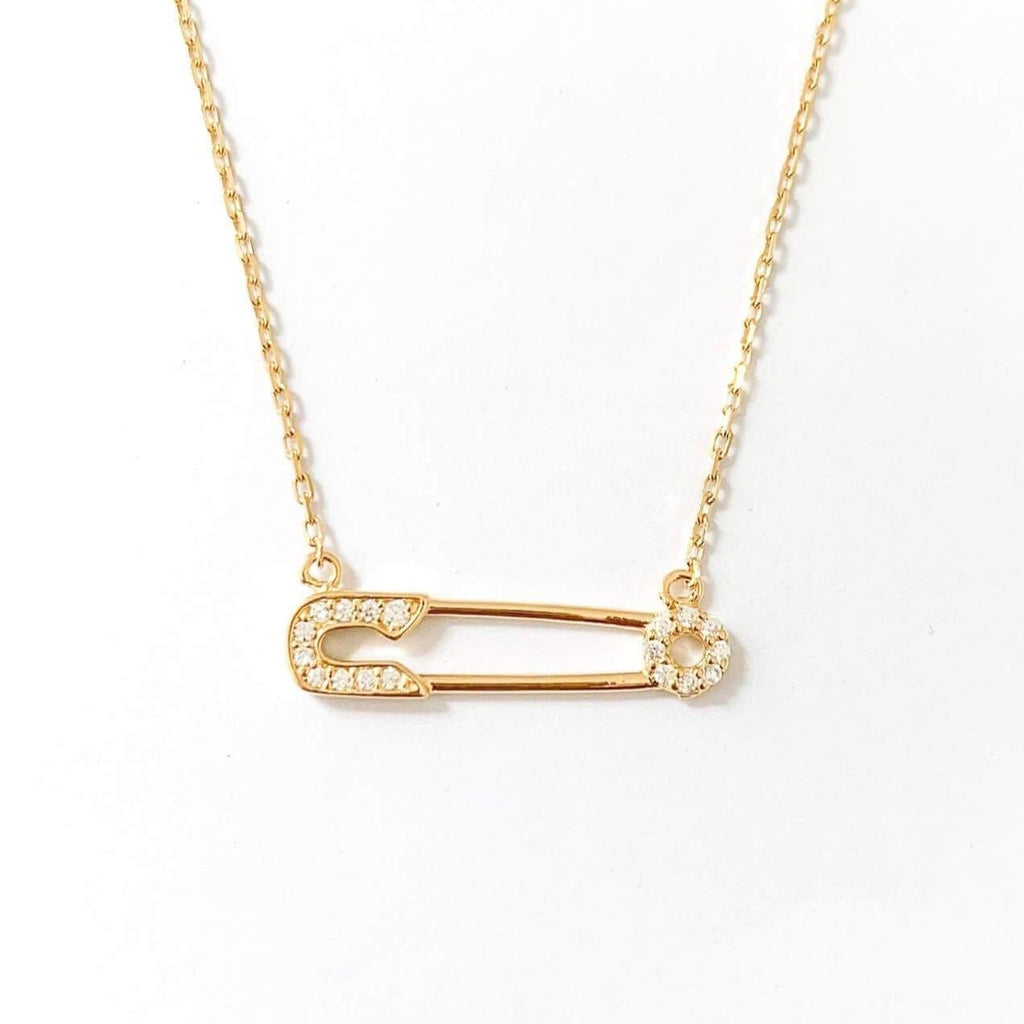 925 Sterling Silver Plated with 14k Gold Pave Safety Pin Necklace. Gold Pave Safety Pin Connected by a gold chain on the top of each safety pin end. The necklace is shot on a white background. This necklace also comes in silver.