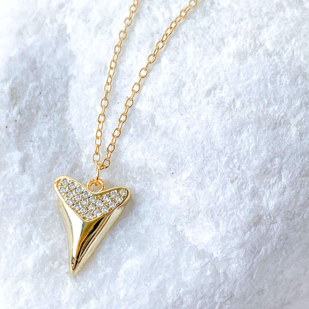 Whim Collections Mesa Gold Vermeil Shark Tooth Necklace shot close up and draped over a white stone.