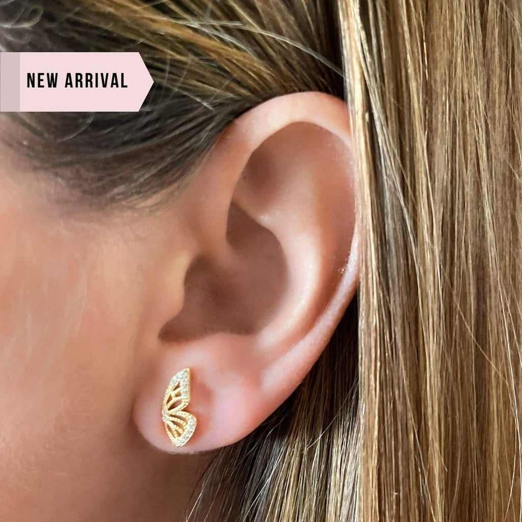 "Whim Collection Gold Butterfly Ring Shown on Model. Photo is zoomed in on left ear. Earring Features Right Butterfly wing facing upright on earlobe. Model has dark blond hair and photo reads ""New Arrival"". Photo was added to site on January 12 2020."