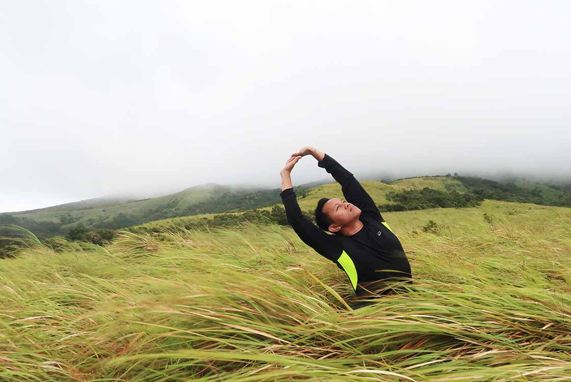 Man Stretching In Grassy Field from Hemp Oil Pain Relief Article