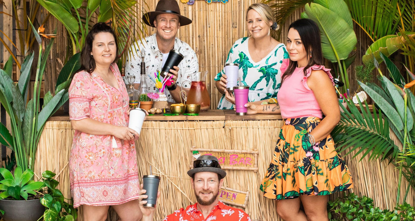 This Photo is Of MontiiCo Staff Standing in Front of a Tiki Bar Holding MontiiCo Products