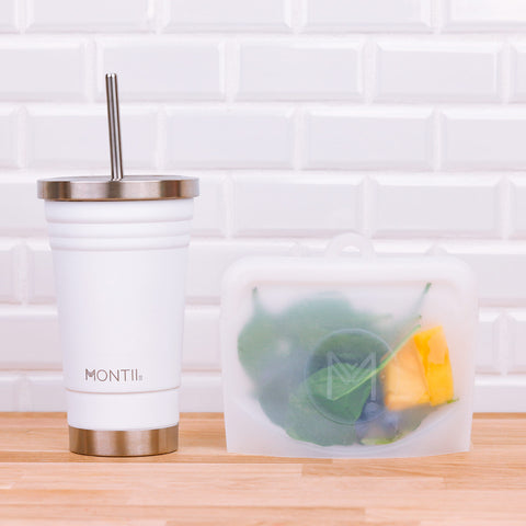 This is a photo of a MontiiCo white smoothie cup beside a clear snack bag with fruit and spinach in it.