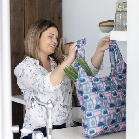 This is a photo of a lady in the kitchen unpacking her groceries out of a MontiiCo Bloom shopper bag.