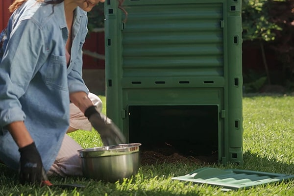 Woman getting soil from compost bin