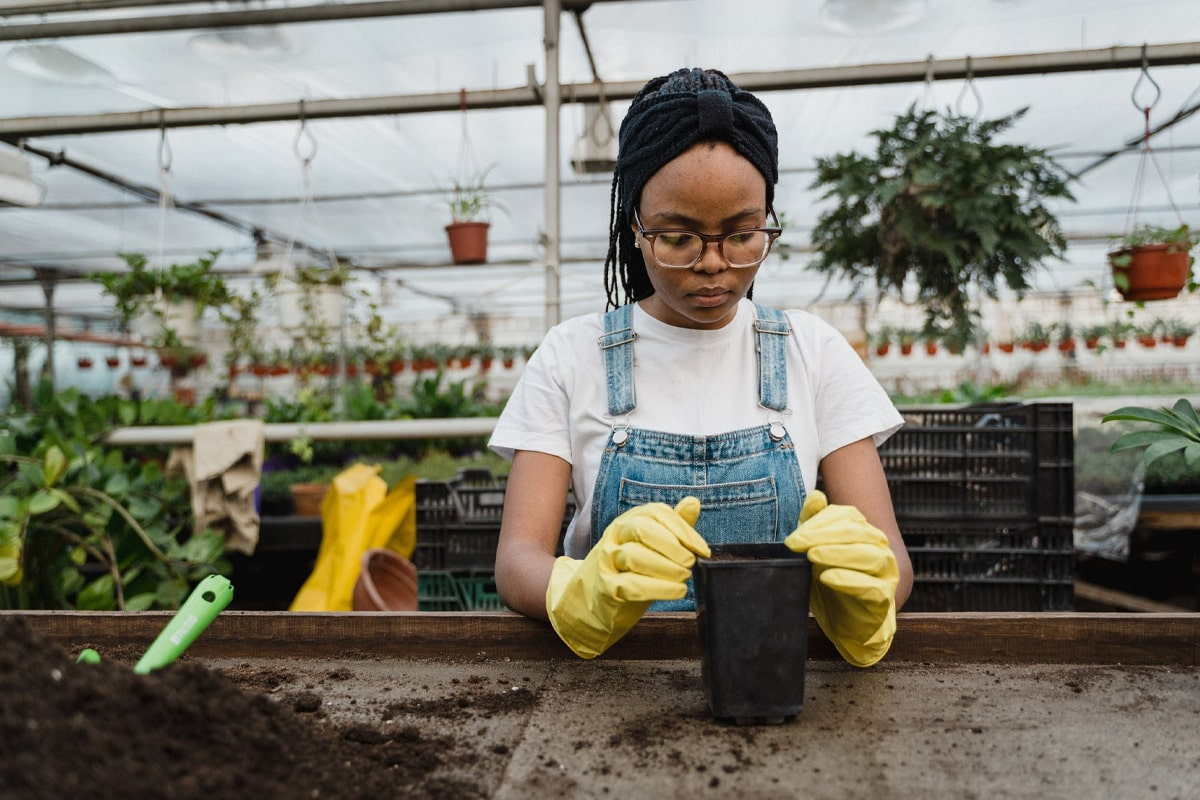 Young woman planting using her yellow gloves