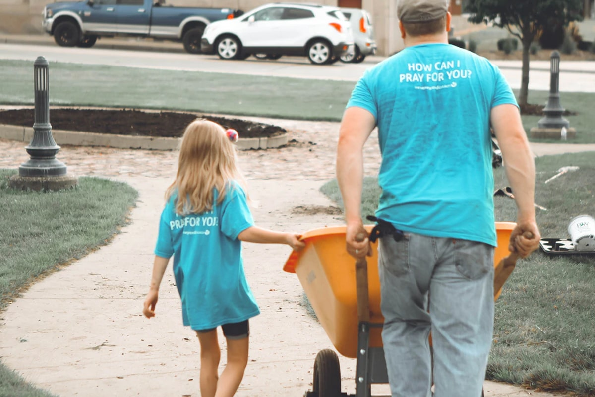 Father and daughter pushing wheelbarrow