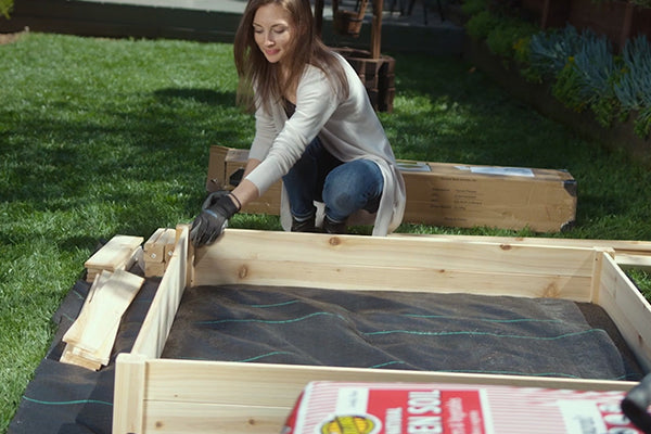 Woman installing Raised bed and landscape fabric
