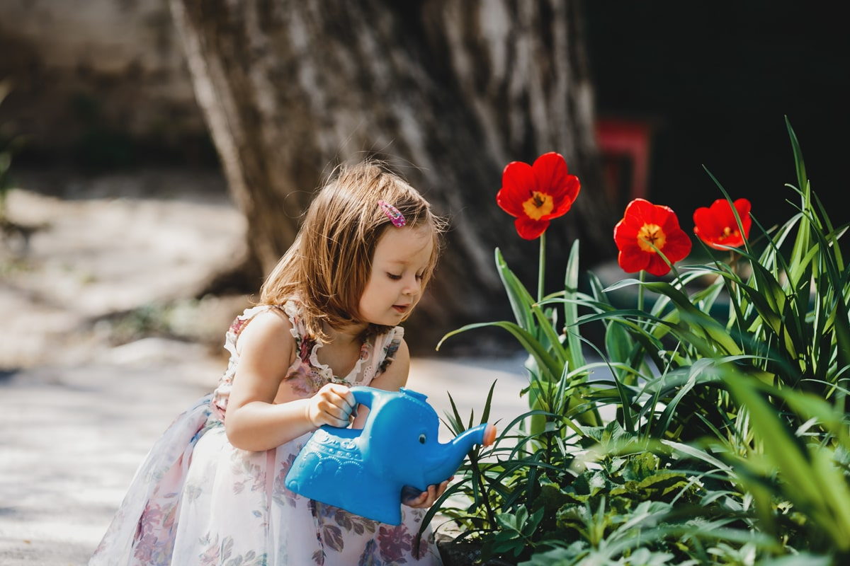 A young girl watering the plants