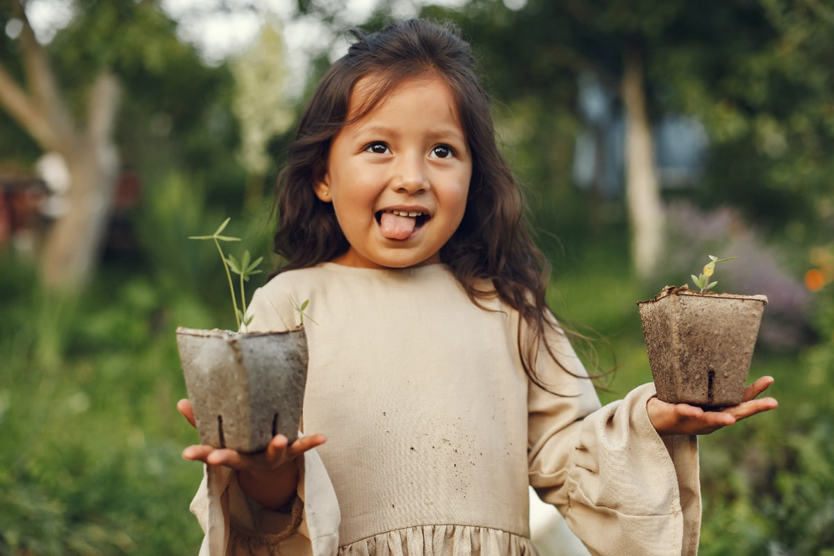 A child holding two potted plants in her hands.