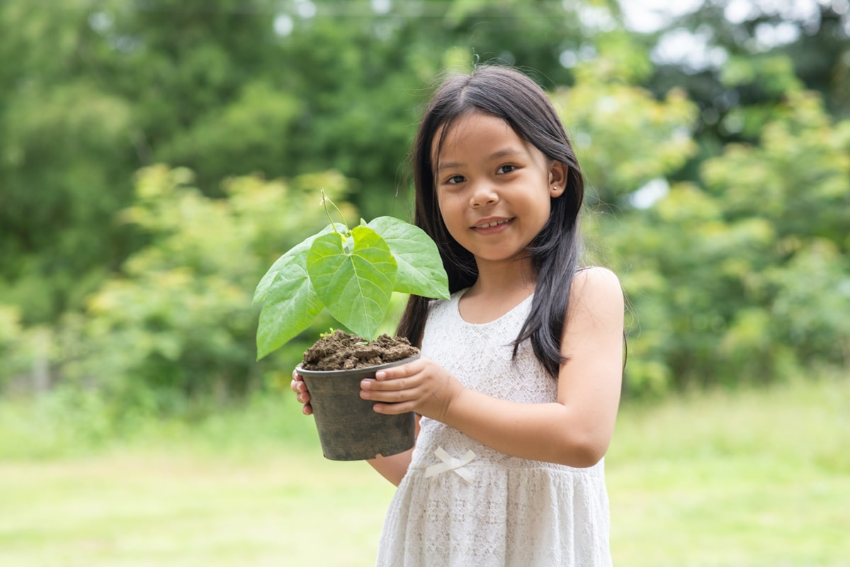 A child smiling while holding a potted plant