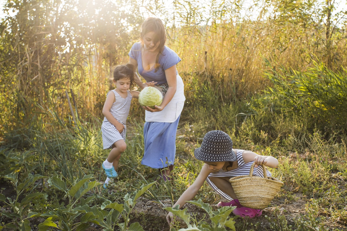2 kids along with their mother harvesting vegetables