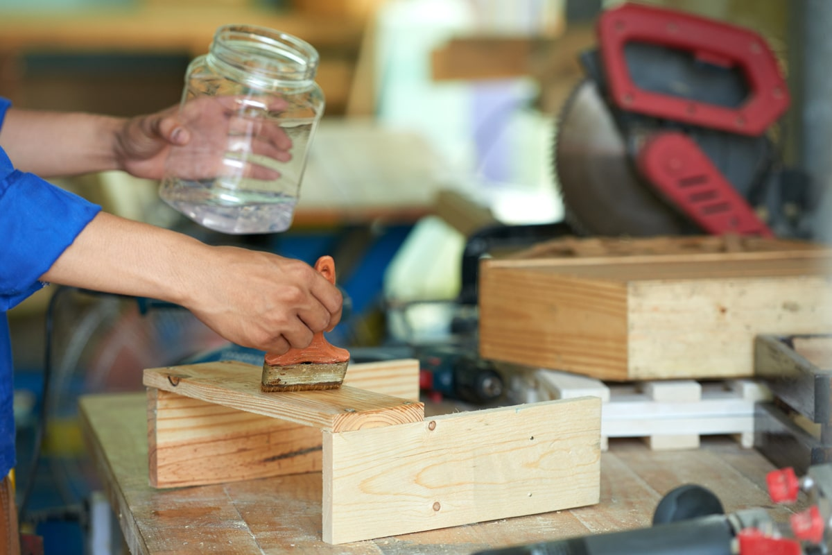 A person applying chemical to the wood