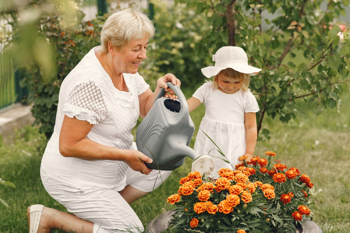 A grandmother and a child watering the plants