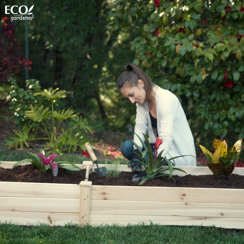 A woman planting in an Ecogardener Raised Bed.