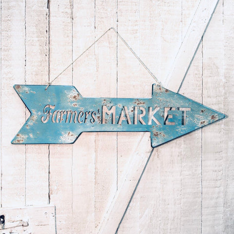 Blue metal arrow sign with farmers market cut out from One Cottage Way
