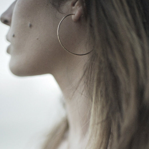 Model wearing hammered gold hoop earrings
