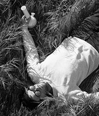 Liam Kaczmar founder of Summerland, lying in a field holding a ceramic bong.