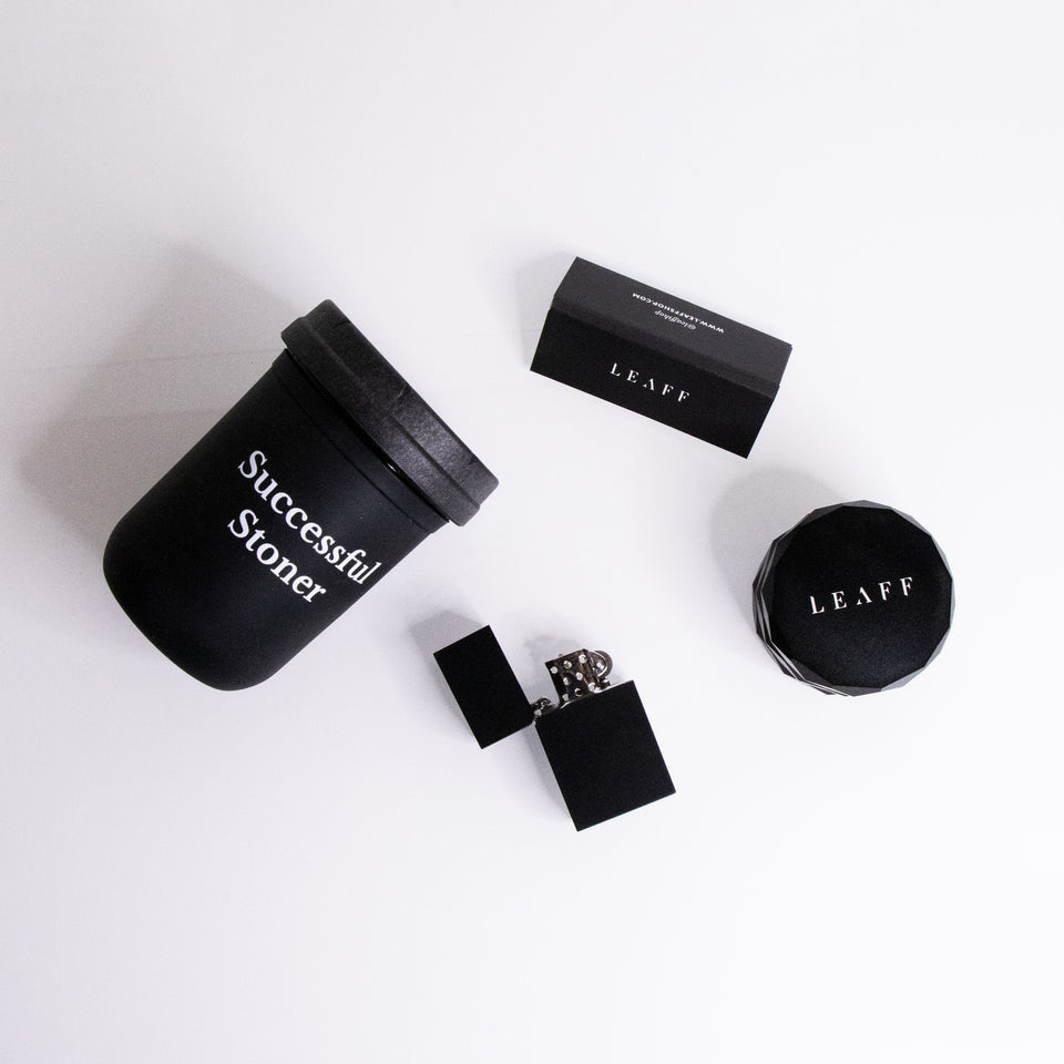 Matte black cannabis accessories. Stash jar with rolling papers, lighter and grinder.
