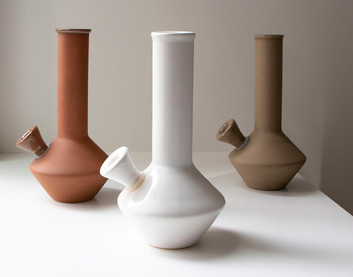 Three ceramic bongs in white, terracotta and stone.