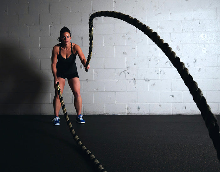 Woman using battle ropes during a workout.