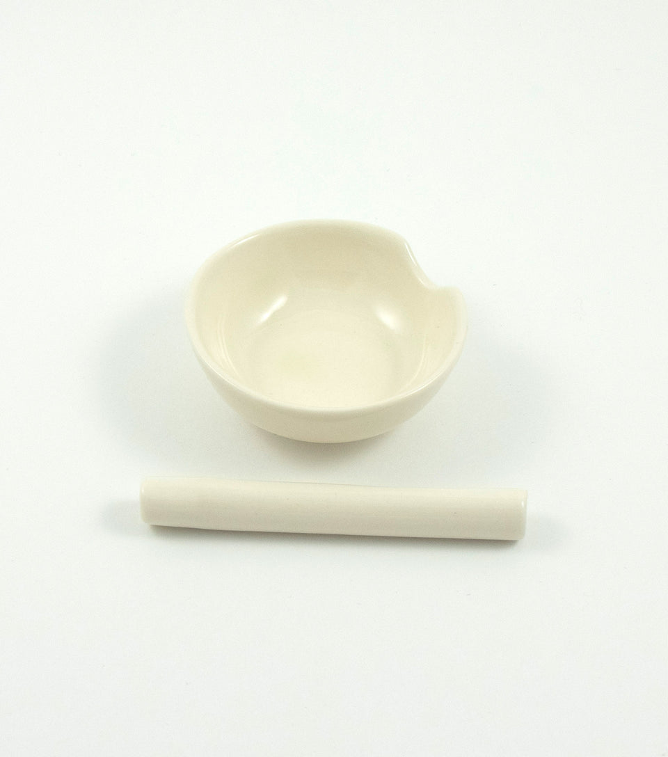 White ceramic cannabis chillum sitting next to small white ashtray.