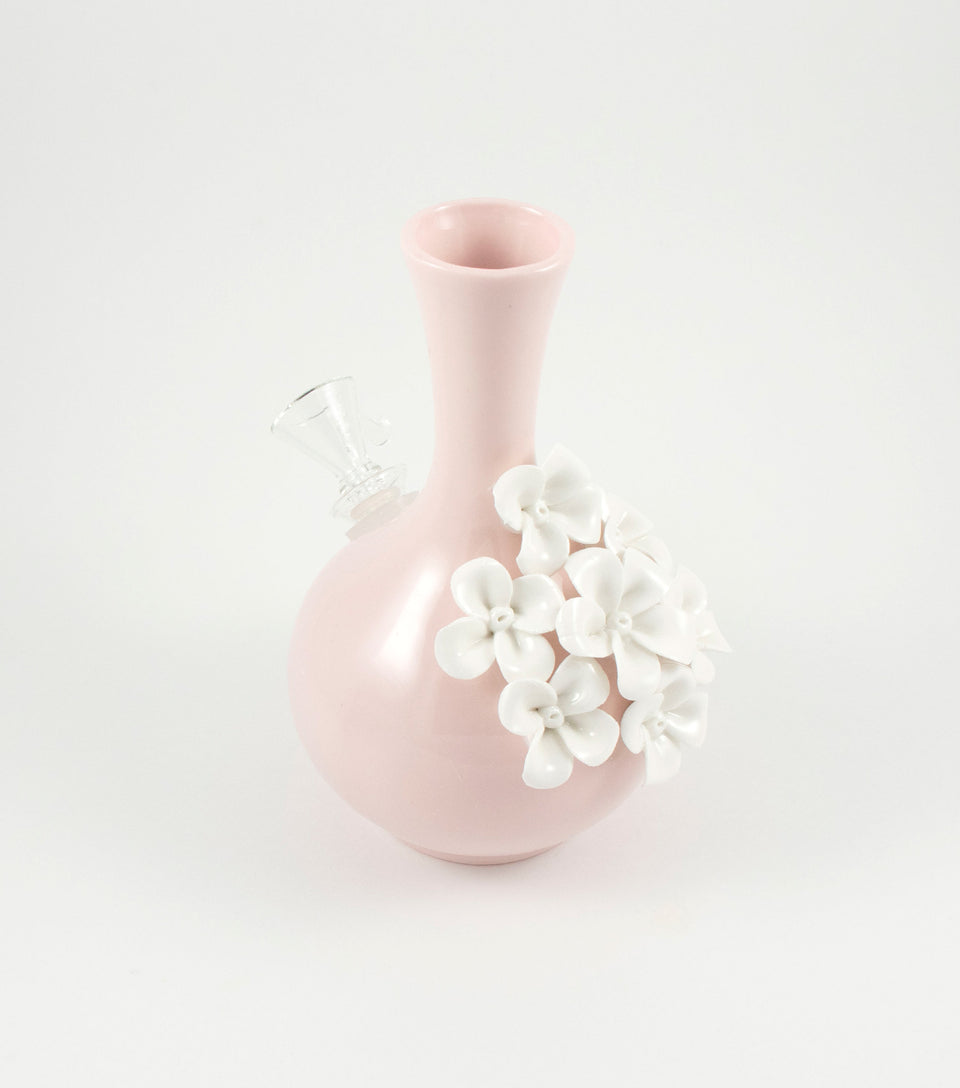 Small pink ceramic bong with white flowers.