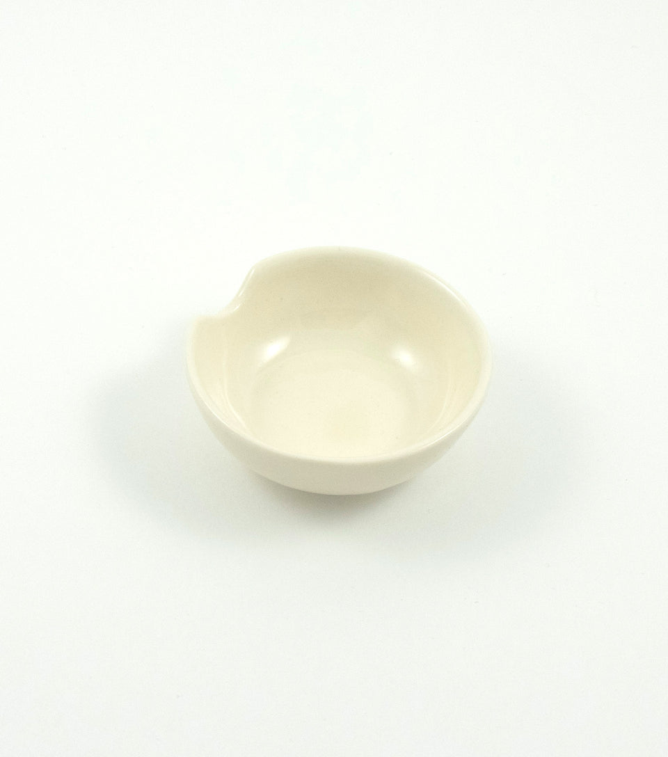 Small white ceramic ashtray.