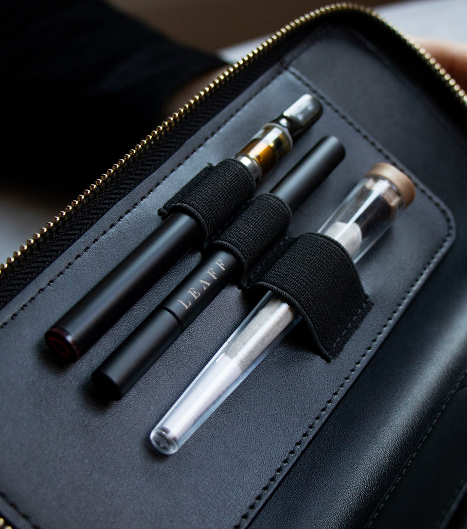 Black leather wallet with 3 elastic loops holding a vape pen, a pipe and a tube with cannabis joint inside.