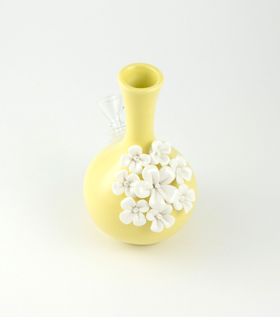 A yellow bong vase with white flowers