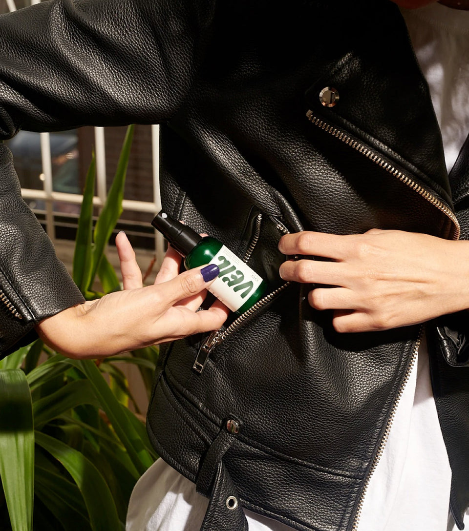Woman putting bottle of natural smoke eliminator in her pocket.