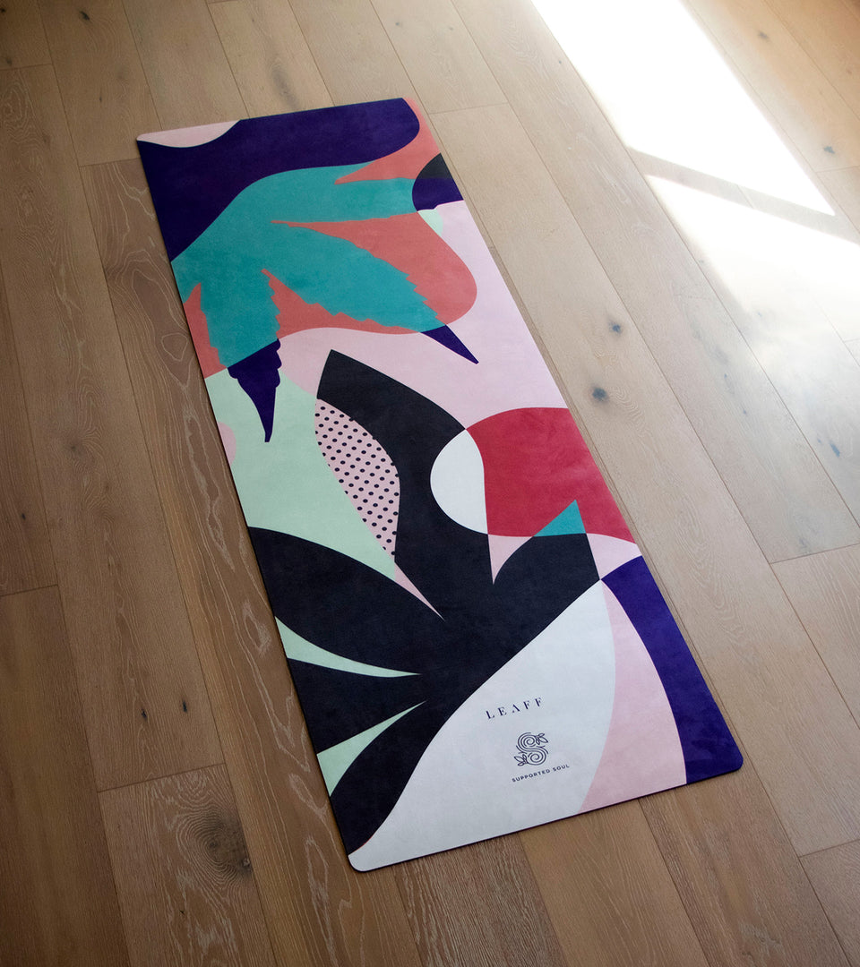 Yoga mat with cannabis leaf design on wooden floor.