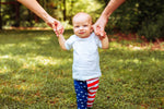 baby boy standing in white tee and stars and stripes leggings