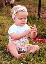 baby girl wearing sun print bummies and top knot headband