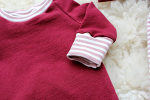 pink and white striped cuffs on cranberry red baby girl shirt