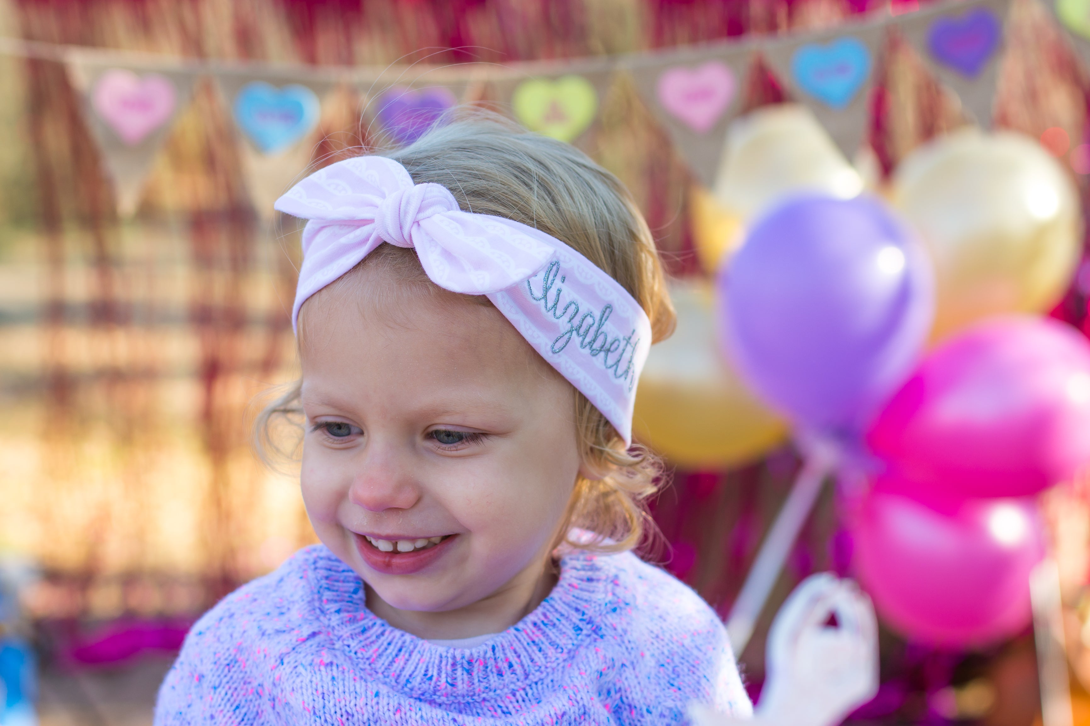 little girl wearing a top knot headband with her name on the side